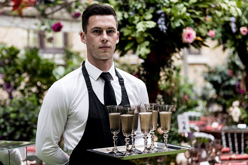 A waiter holding a try with champagne glassed during an event